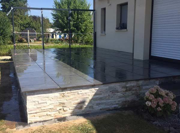 Terrasse en carrelage gris surélevée d'un parement en pierre à Vitré