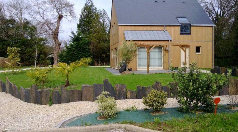 Bordures de pelouse en grandes plaques d'ardoises, arbres et arbustes, allée en gravier devant maison en bois à Laval